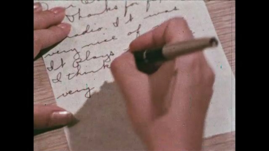 UNITED STATES: 1968: close up of hands writing letter. 'A Very Special Man' title. Man in sailor uniform boards boat. Sailors salute each other on ship. Man goes through door on ship.
