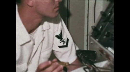 UNITED STATES: 1968: Sailor works on ship. Close up of sailor's badge. Sailor sits down in cabin and takes off hat. Sailor writes on paper, Sailor listens to message on tannoy.