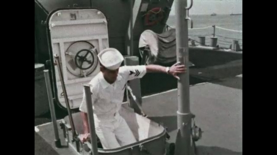 UNITED STATES: 1968: Sailors climb out of hatch onto deck of ship. Sailors line up in front of flag. Sailors salute.