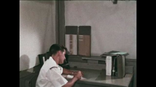 UNITED STATES: 1968: sailors speak in cabin. Man writes letter in cabin.