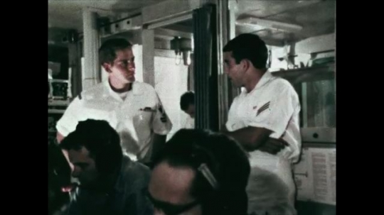 UNITED STATES: 1968: Officers talk on board military ship. Sailor looks at radar on ship