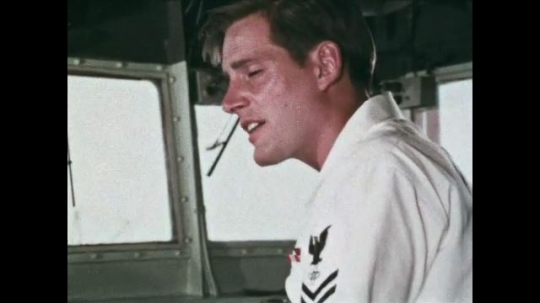 UNITED STATES: 1968: Navy men talk in room on ship. Sailor looks at radar on ship.