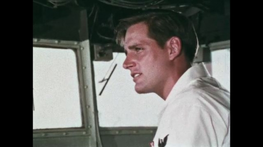 UNITED STATES: 1968: Navy men talk in room on ship. Sailor looks at radar on ship. Sailors plan pilotage on nautical charts. Man operates buttons on switchboard.