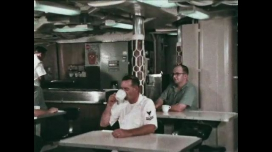 UNITED STATES: 1968: sailors drink tea in ship canteen. Man sits next to colleague in mess room.