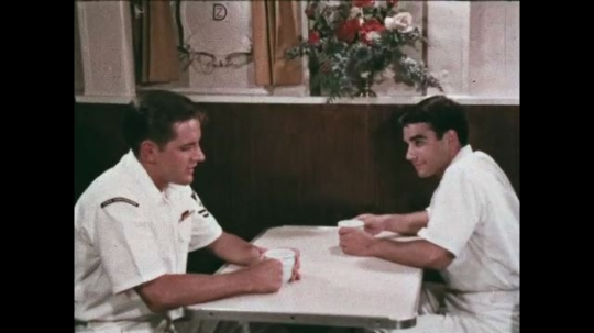 UNITED STATES: 1968: sailors talk at table in canteen. Men smile as they talk. Sailors drink tea. Men make notes in meeting.