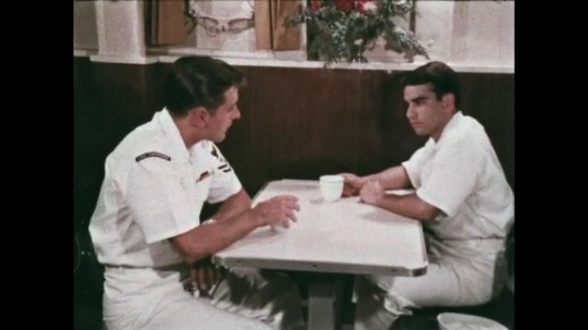 UNITED STATES: 1968: two sailors talk and drink tea in mess room. Navy man teaches from blackboard.