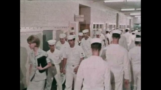 UNITED STATES: 1968: sailors walking in corridor. Navy recruits learn trades at academy. Man presses button on printing machine.