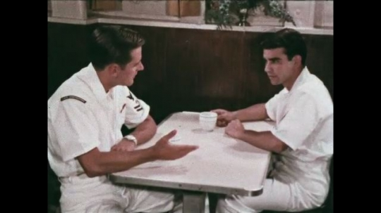 UNITED STATES: 1968: sailors talk and drink tea in mess room on ship. Officer gives talk to navy recruits in classroom Naval recruits in class.