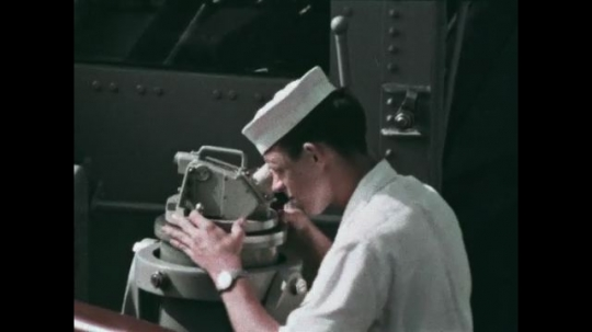 UNITED STATES: 1968: sailor looks through scope on ship. Men tidy away ropes on ship. Flags fly on ship deck.