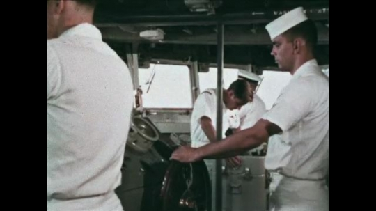 UNITED STATES: 1968: man checks radar on ship. Deck of ship with flags.