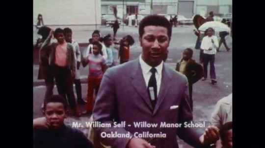 United States: William Self talks to camera as children play in school yard.
