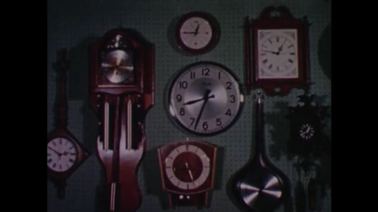 UNITED STATES 1960s: Clocks on wall / Cuckoo clocks on wall / Close up of clock chiming / Close up of pendulum, tilt up to clock face.