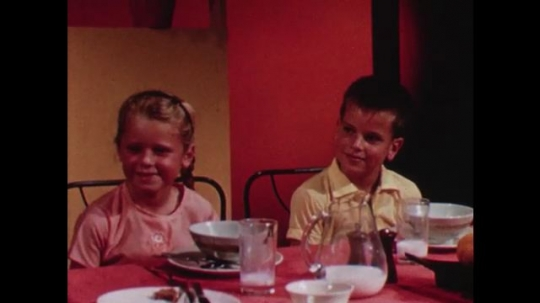 UNITED STATES 1960s: Boy and girl at table / Woman gives lunchboxes to kids, kids exit / Kids sit at desks / Clock on wall / Rear view of kids looking at flag.