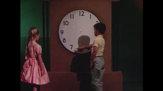UNITED STATES 1960s: Boy and girl look at clock face, boy points to numbers / Boy points to numbers on clock face.