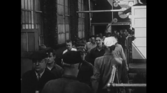 UNITED STATES, 1940s: Men leave work after finishing for the day. Men leaving factory gates. Two men stop and chat as they leave factory gates.