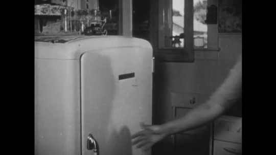 UNITED STATES, 1940s: Lady opens fridge door. Man pretends to shave boy's face as he shaves his own.
