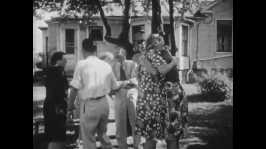 UNITED STATES, 1940s: Friends and family greet each other in garden.