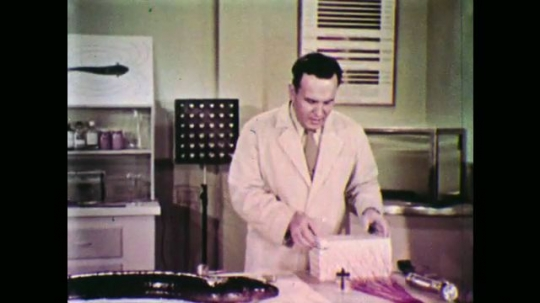 UNITED STATES: 1950s: Man in lab opens and closes lid on box. Man talks to camera.