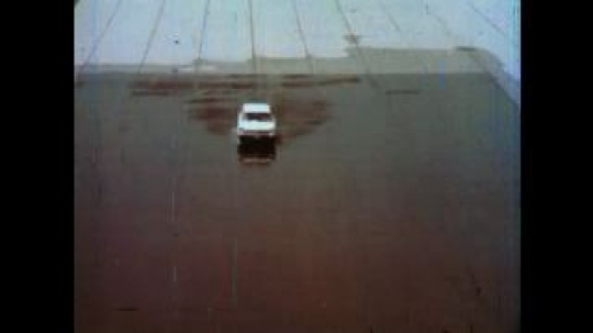 United States: 1980s: car travels across wet surface and slides. Car drives through obstacle course on wet road. Car knocks over cones. Cars slides on wet surface