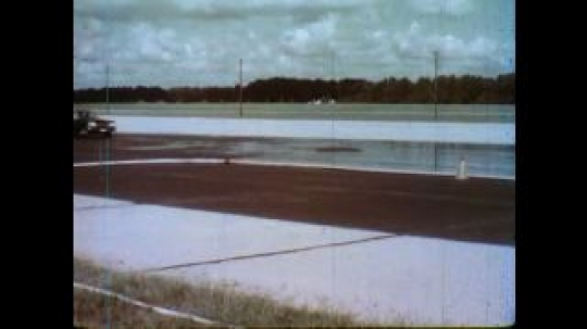United States: 1980s: Two cars travel parallel along wet surface. Two cars stop in wet conditions.