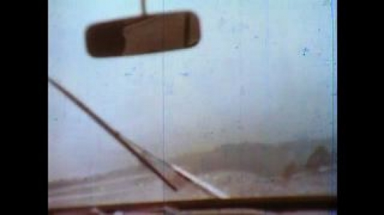 United States: 1980s: view through wipers on car windscreen. Cars and lorries drive up hill in rain.