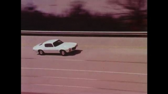 UNITED STATES: 1960s: Cars test driven on proving ground track.  Engineers study cars on track