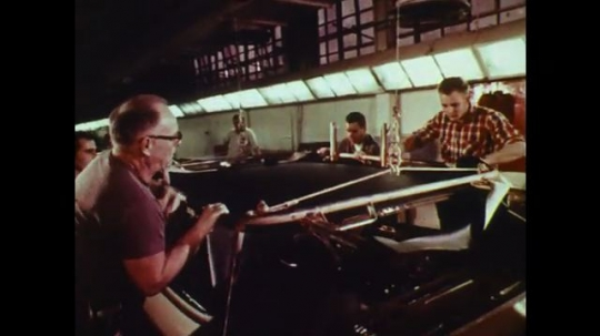 UNITED STATES: 1960s: workers assemble car. Lady inspects car interior