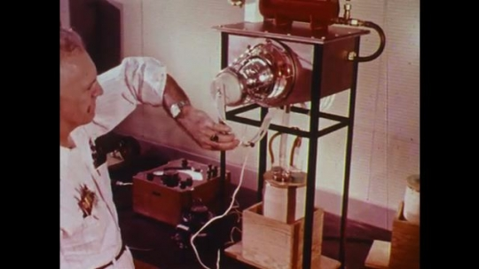 UNITED STATES: 1960s: man investigates air pollution in lab at car manufacture plant. Internal combustion engine development. Alternative energy for vehicles research.