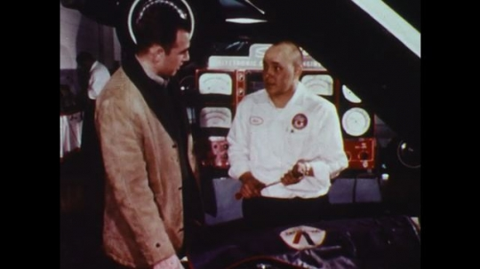 UNITED STATES: 1960s: maintenance specialist talks to man about car. Drawings of car design.