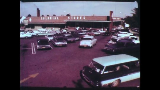 UNITED STATES: 1950s: Colonial stores car park. Man talks to camera. Man in supermarket.
