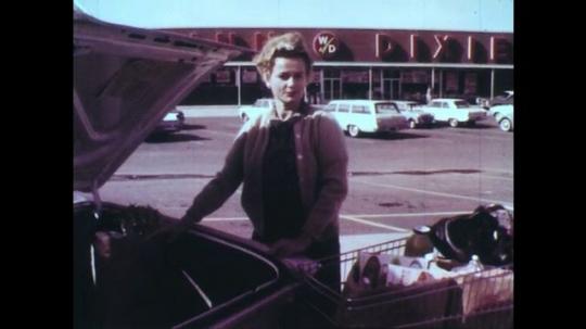 UNITED STATES: 1950s: lady talks to camera in supermarket car park. North Carolina Store. Jars on shelf. Processed food. Ham on shelf.