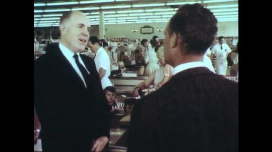 UNITED STATES: 1950s: Man talks to camera. Man in supermarket. Food on supermarket shelves. Eggs on display.
