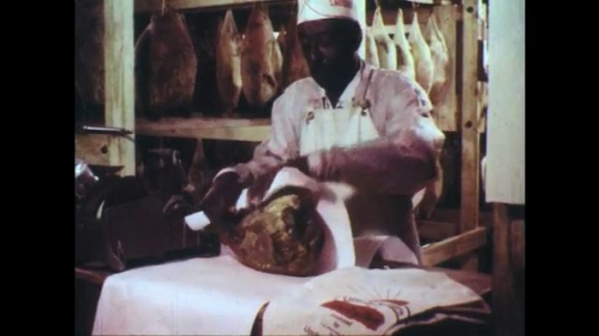 UNITED STATES: 1950s: country cured hams. Man wraps ham. Man tests ham on rack.
