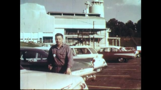 UNITED STATES: 1950s: man stands in car park. Man talks to camera.