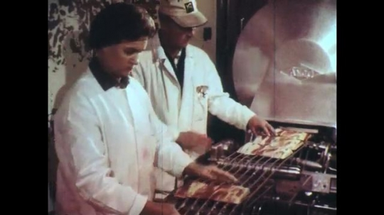 UNITED STATES: 1950s: factory workers process food. Freshly cooked chips. Vegetables on conveyor system.