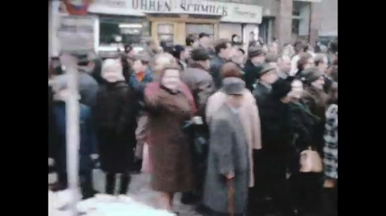 UNITED STATES 1960s: Tracking shot, crowd on street / Crowd on street / Man standing on car, speaking / View of street from car.
