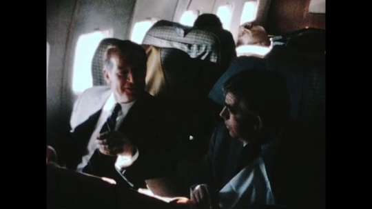 UNITED STATES 1960s: Men talking on plane, zoom in / John Erlichman eating on plane, waves camera away, zoom in on food / Nixon shakes hands with officials on tarmac.