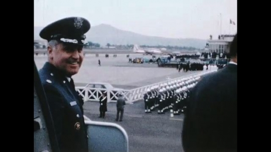 UNITED STATES 1960s: Ralph Albertazzie and John Erlichman talking on steps of plane, military band in background.