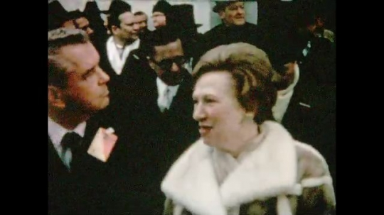 UNITED STATES 1960s: Rose Mary Woods talks to man, pan across crowd at Nixon inauguration / View of flag waving.