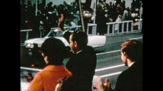 UNITED STATES 1960s: Rear view, Richard and Patricia Nixon wave from parade box / Float passes in parade, people singing on float.