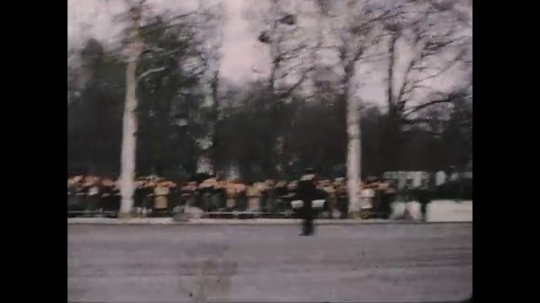 UNITED STATES 1960s: Tracking shot from car, crowd on lining street, view of motorcade driving through Paris.