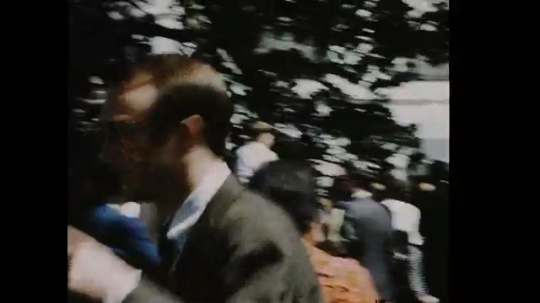 UNITED STATES 1960s: Man outside White House, walks off screen / Man looks at White House, turns to camera, zoom out, pan across White House.
