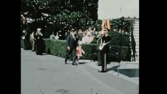 UNITED STATES 1960s: Crowd outside White House, man walks with girl, zoom in on man / Richard Nixon and King Hussein on stage, press in foreground / King Hussein speaking.