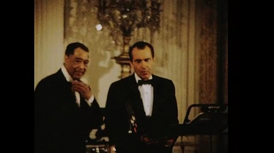 UNITED STATES 1960s: Richard Nixon and Duke Ellington on stage, zoom out / Nixon reading award on stage / Nixon gives award to Ellington, crowd stands and applauds.