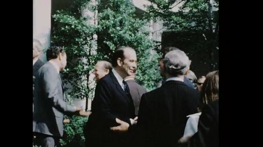 UNITED STATES 1960s: Robert Ellsworth talking to men outside White House, Richard Nixon in background / Nixon speaks on stage, zoom in / Warren Burger walks on stage, shakes hands with Nixon, zoom in.