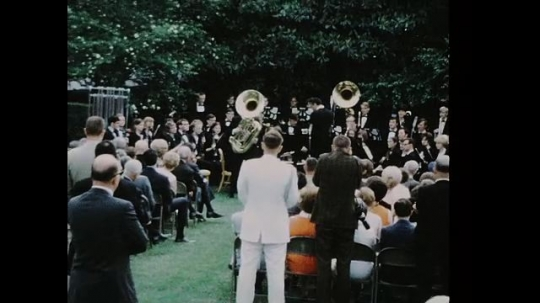 UNITED STATES 1960s: Band performing in White House garden, zoom out to crowd / Zoom in, Richard Nixon shakes hands with man, tuba player.