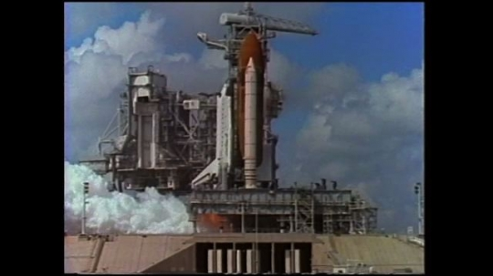 UNITED STATES: 1980s: space ship takes off from launch pad. Space shuttle attached to solid rocket. Slow motion space ship launch.