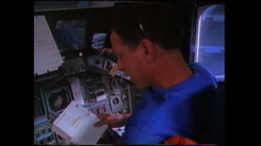 UNITED STATES: 1980s: astronaut goes through check list in space shuttle. Astronaut checks switches and monitors.
