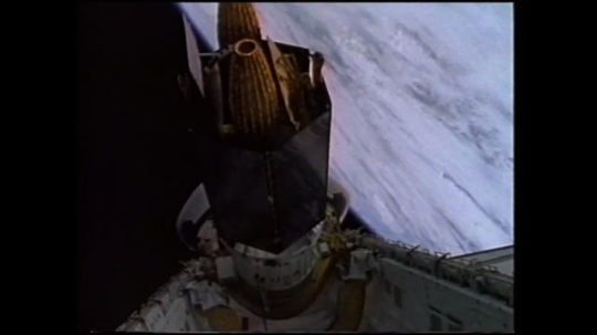 UNITED STATES: 1980s: satellite attached to space shuttle in space. Astronaut checks switch control.