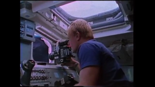 UNITED STATES: 1980s: astronaut documents deployment from space shuttle window. Astronaut checks dashboard.
